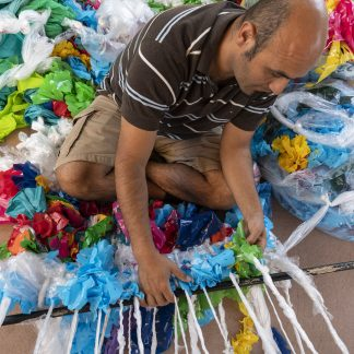 Many sitting on floor weaving together plastic pieces of many colors, surrounded by plastic bags, flags, and sheets of plastic.