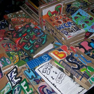 Table full of stacks of books with brown paper covers painted with colorful letters.