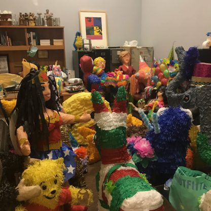 Room filled with many colorful pinatas of people and animals.