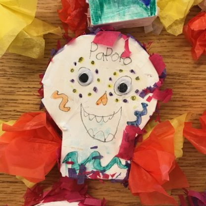 Smiling face with googly eyes on white skull-shaped paper. Colorful tissue paper glued around.