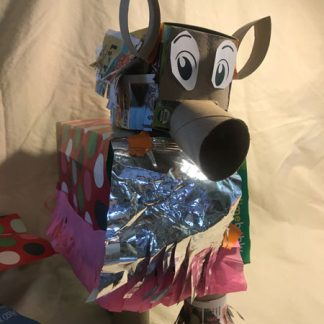 Animal made of boxes, toilet paper rolls, with big ears, big printed eyes, and body covered in cellophane, wrapping paper, and tissue paper.