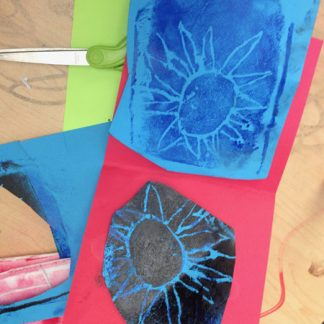 Bright paper with ink prints of flowers on pieces.