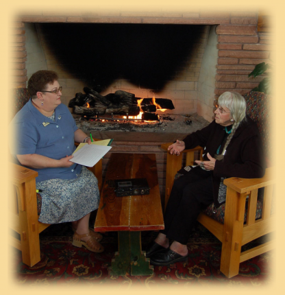Two people talking and holding papers in front of fireplace.