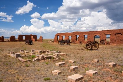 Old fort wall, wagons in field around wall, stone bricks in foreground. Partly cloudy sky.