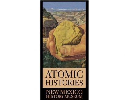 Atomic Histories. New Mexico History Museum. Large hand holding rock with desert scenery and building in background.