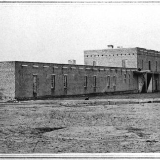 Black and white old photo of fort. Long low building with one section on second story. Many windows.