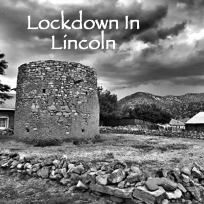 Lockdown in Lincoln. Large, old round structure made of stacked stone bricks. Rocks in line across ground. Stormy sky. Mountains in background.
