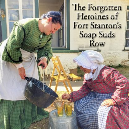 The Forgotten Heroines of Fort Stanton's Soap Suds Row. Two people dressed up in old-fashioned plaid dresses, aprons, and a bonnet. Pouring from a large pot, with glasses of liquid in front of them on an over-turned bucket.