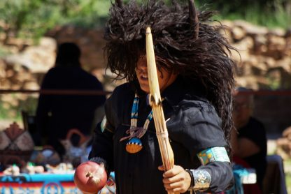 Person with large dark brown hairy head covering with horns. Holding wooden staff and arrows. Wearing black clothing with beaded necklace with shell, armband, and silver and turquoise wrist cuff.