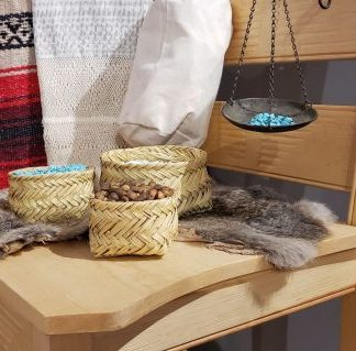 Table with baskets filled with seeds and turquoise stones. Animal fur. Red, black, and white striped blanket, white woven material, metal hanging basket with turquoise hang behind table.