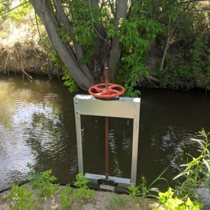 Small metal structure with wheel next to water in acequia
